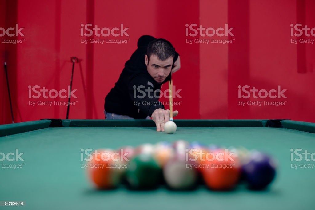 Attractive young man is playing billiard