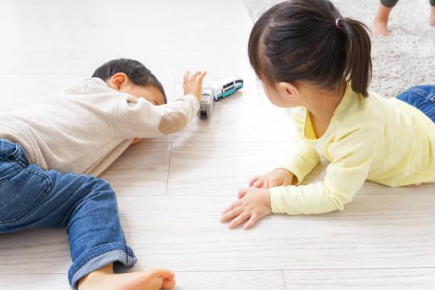 jungen und mädchen spielen - küstenfamilienzimmer stock-fotos und bilder
