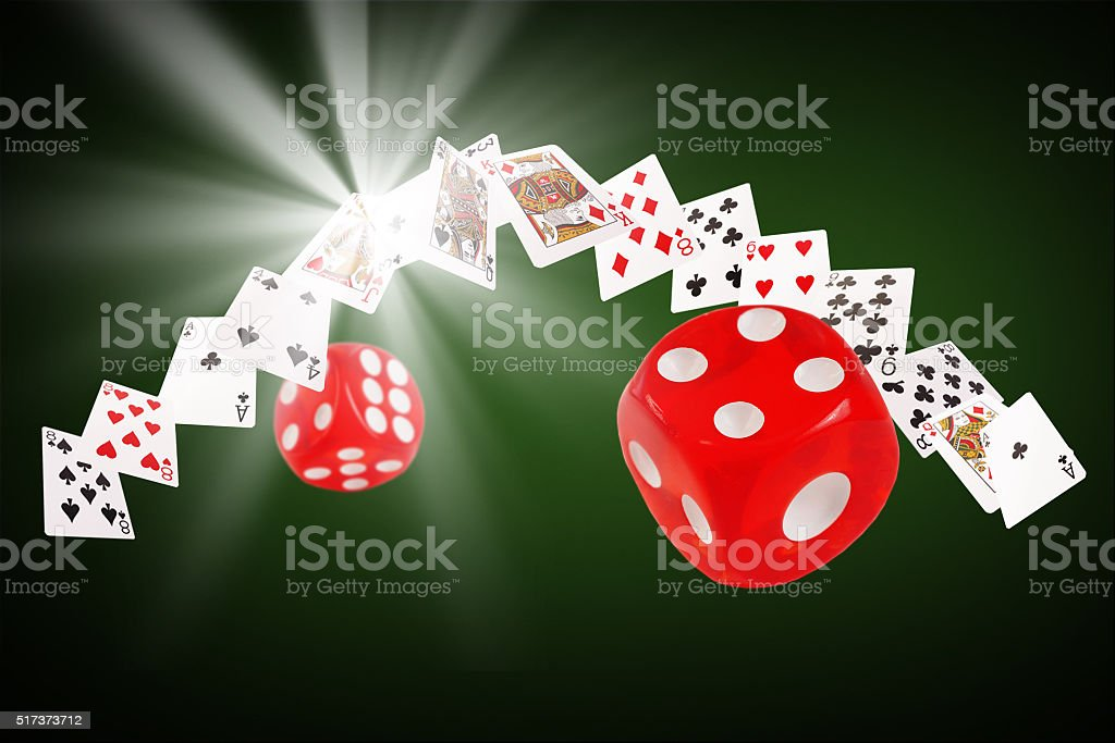Playing cards and dice flying at the poker table stock photo