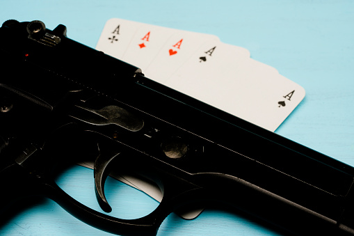 istock playing cards and gun 949500618
