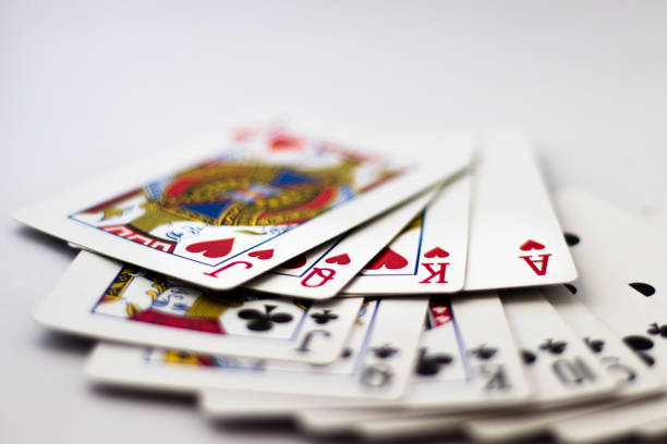 Playing Cards fanned out: Suit of Spades, Clubs and Diamonds fanned out over white background. Gambling, Poker, Win, Lose, Chance, Gambling, Money, Red, Black, Jack, Queen, King Playing cards with banknotes and coins for gambling playing card stock pictures, royalty-free photos & images
