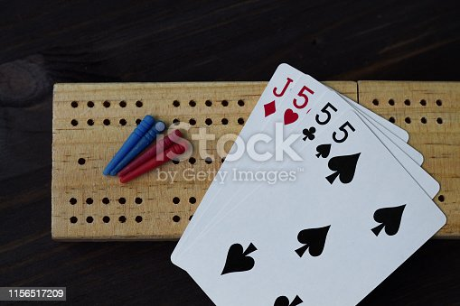 istock playing cards on black background with cribbage board 1156517209