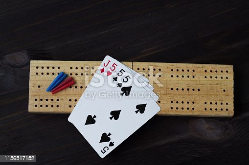 playing cards with cribbage board on black background