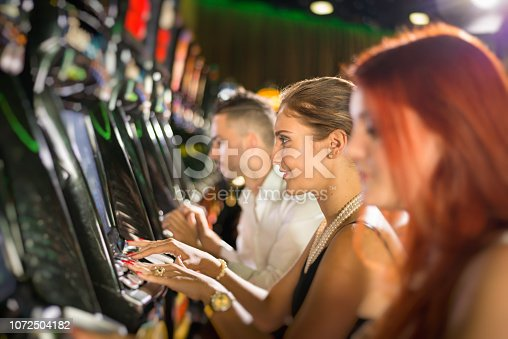 Young adults playing slot machines in a casino.