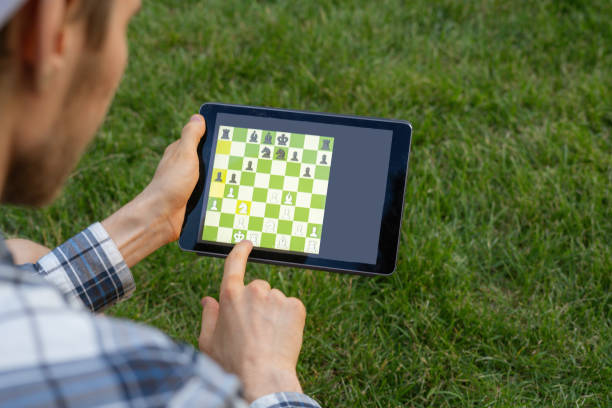 playing chess on a digital device outdoor, mental activity stock photo