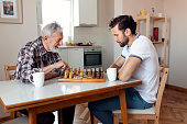 Adult Son and Senior Father Playing Chess Together on Weekend at Home. Father and Son Playing Chess in the Livingroom