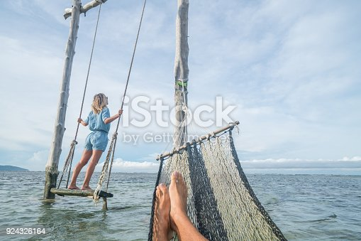 910783248 istock photo Playing couple by the beach, swing and hammock relaxation time 924326164