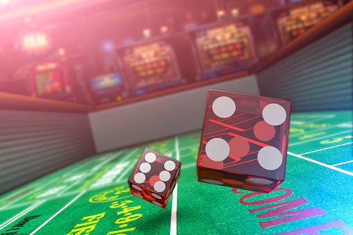 A close up view of dice being rolled on a craps table in a casino with slot machines in the background.  Please see my portfolio for other gambling related images.