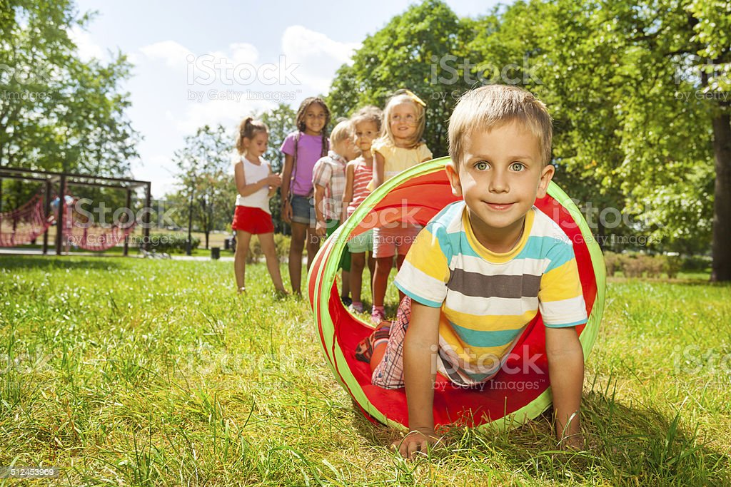 Playing crawling though tube on the lawn stock photo