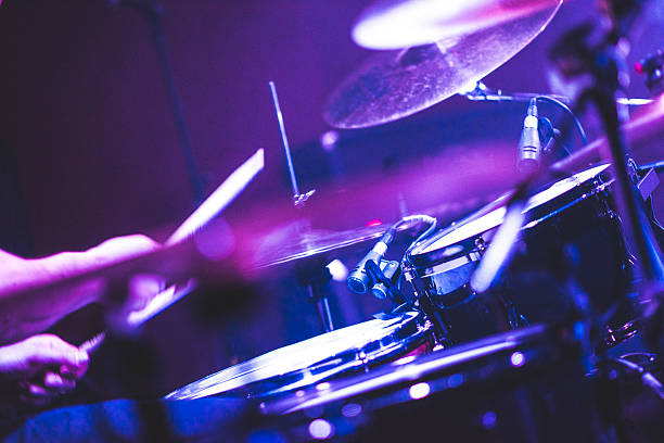 Playing drums on a rock concert Detail shot of drums on a stage on rock concert. There is also some fog in the air. Scene is illuminated with strong blue stage light. drummer stock pictures, royalty-free photos & images