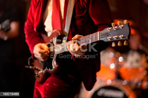 A Rock Guitarist playing guitar at nightclub (Drums in the right background)