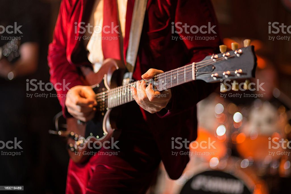 Playing electric guitar on stage stock photo