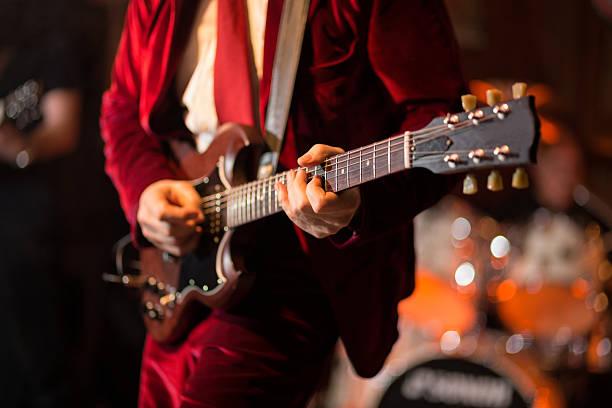 spielt e-gitarre auf der bühne - blues stock-fotos und bilder