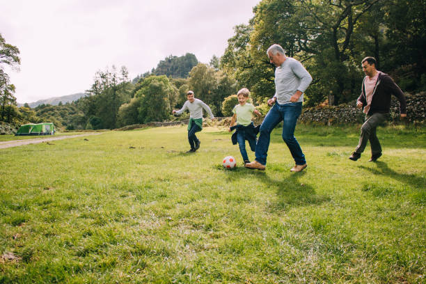 Playing Football With Grandad Three generation family are playing football together in a field. There are two boys, their father and their grandfather. leisure equipment stock pictures, royalty-free photos & images