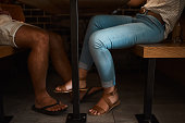 Low angle shot of an unidentifiable young couple's feet as they sit at a cafe table