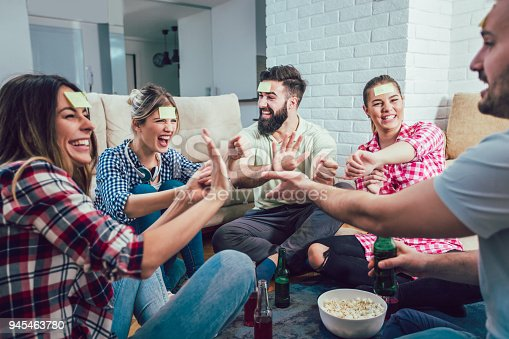 Diverse people playing game guess who and having fun at home