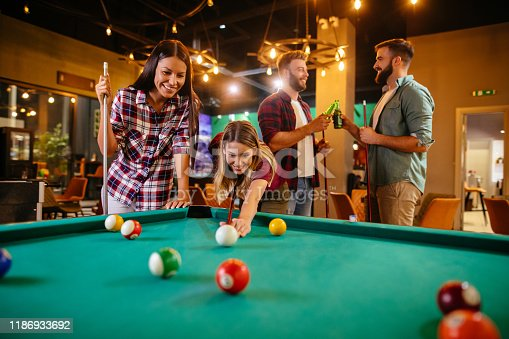 Playing game of pool and drinking beer with friends in local pool hall