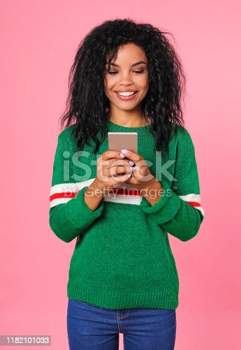 909457386istockphoto Playing games. Beautiful Afro-American woman in a green sweatshirt with white and red stripes is holding a smartphone in her hands and reading something from the screen. 1182101033