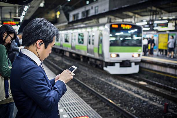 がゲームには、携帯電話の間、列車 - ゲーム ヘッドフォン ストックフォトと画像