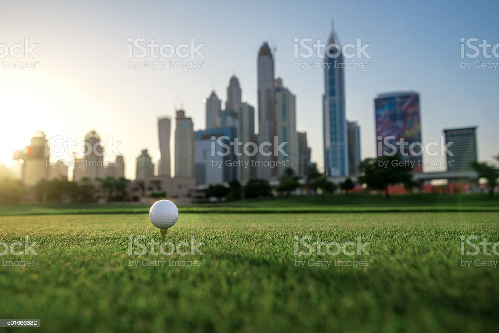Playing golf at sunset. Golf ball is on the tee stock photo