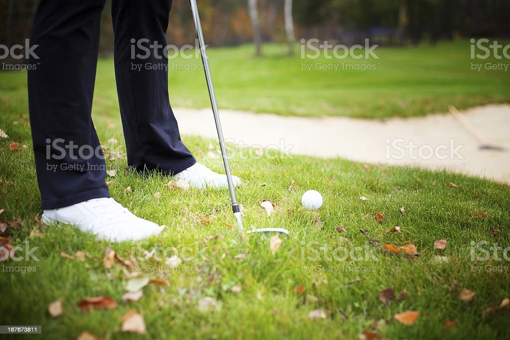 Playing golf with club and ball, preparing to shot