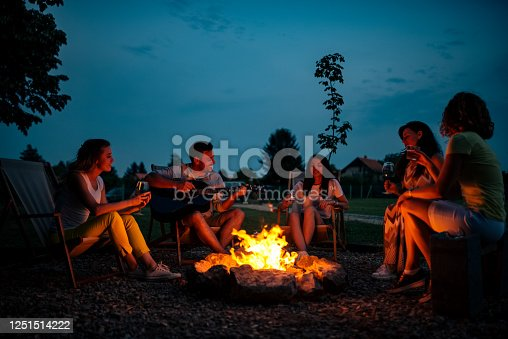 Playing guitar and singing around the bonfire at night.