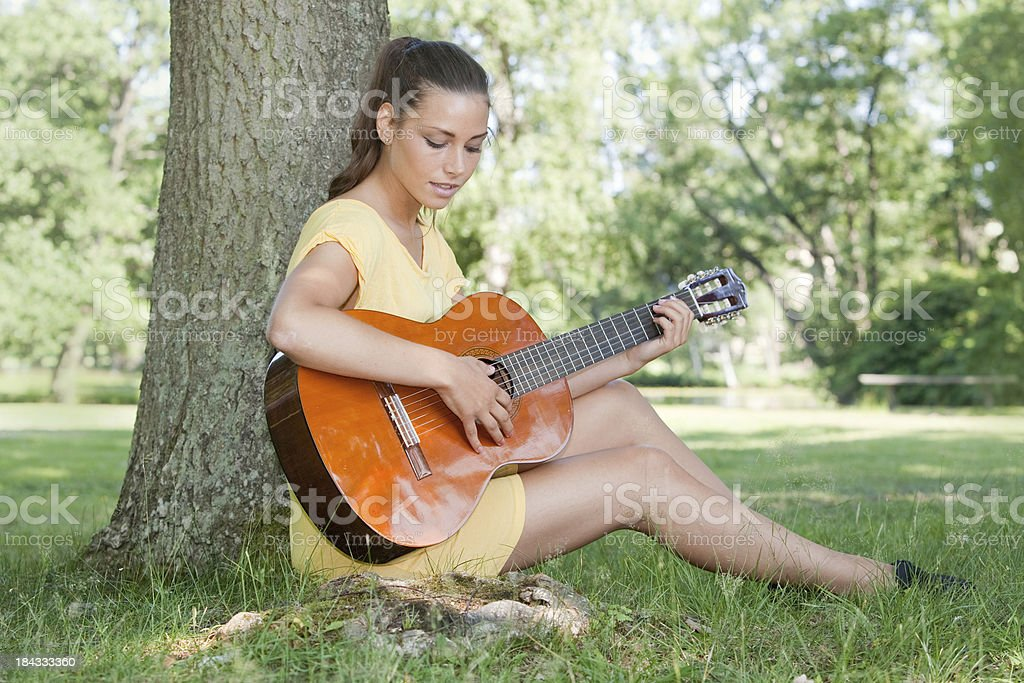 Playing guitar in the park stock photo