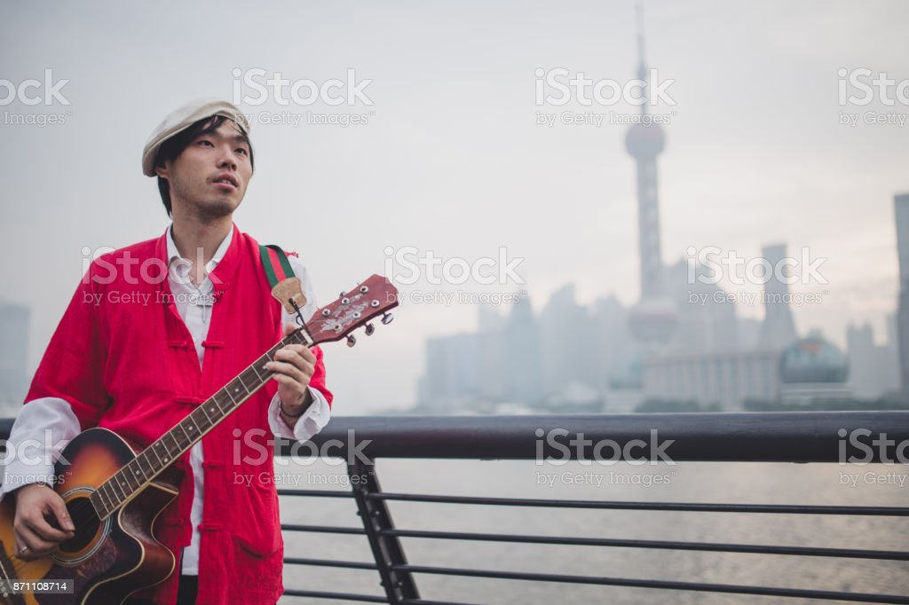 Playing guitar near the river stock photo