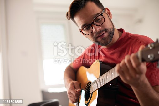 Young casually dressed guy is playing guitar at home.