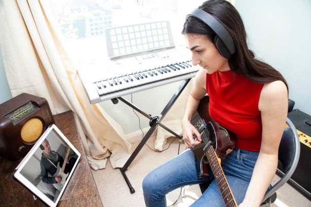 Playing guitar using video conferencing stock photo