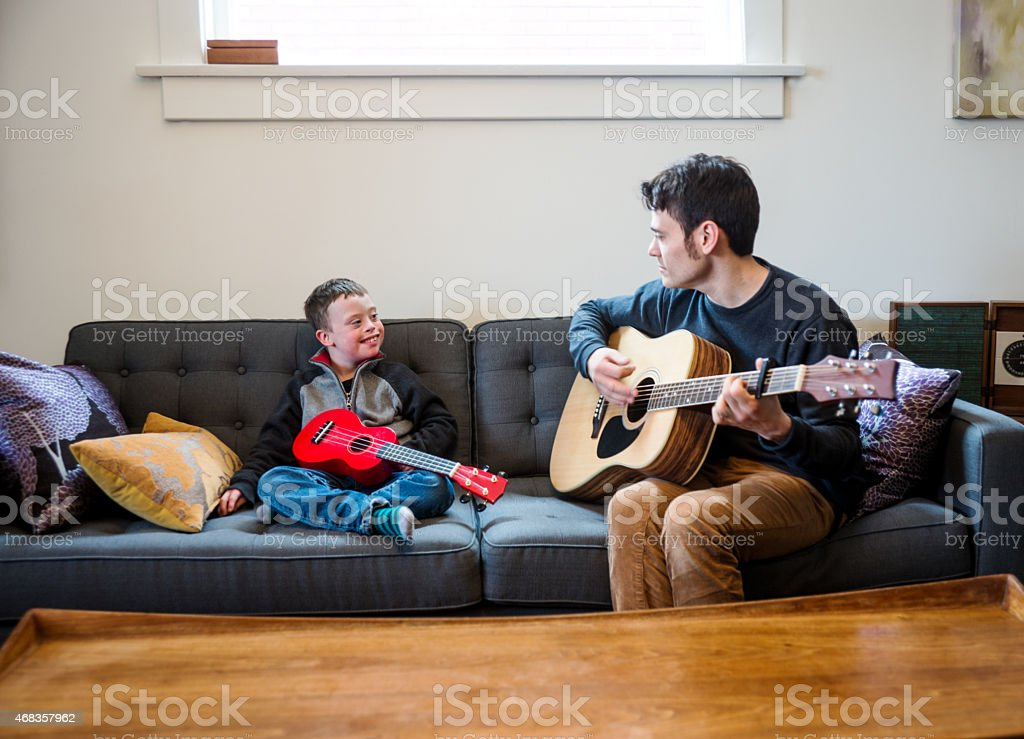 Playing guitar with dad on the couch royalty-free stock photo