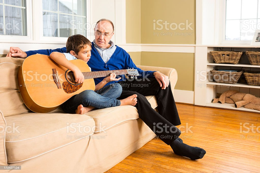 Playing guitar with granddad royalty-free stock photo