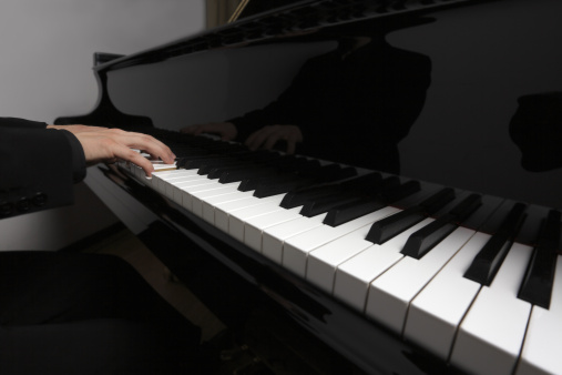 Playing hands of musician on grand piano keys