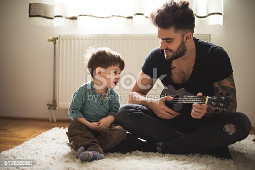 Dad playing some music on a guitar to his son.