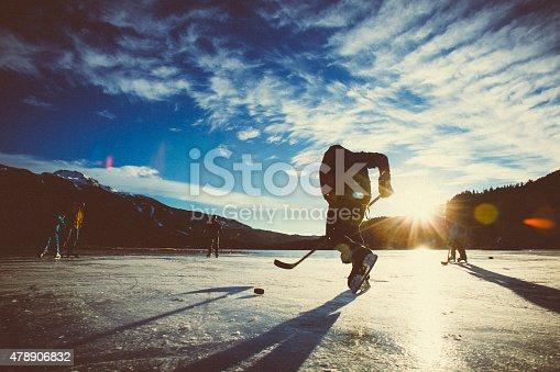 istock Playing ice hockey on frozen lake in sunset. 478906832