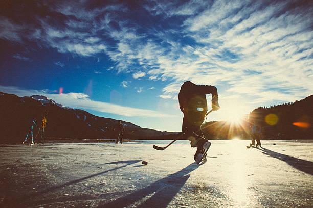 Jogando hóquei no gelo sobre o Lago congelado no pôr-do-sol. - foto de acervo