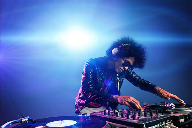 DJ playing in a nightclub with lights behind them nightclub dj playing music on deck with vinyl record headphones light flare clubbing party scene dj stock pictures, royalty-free photos & images