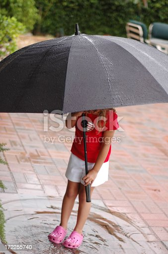 Little girl playing outside in a puddle as it rains.