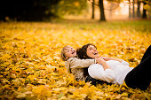 Mother and child having great time playing together in autumn nature