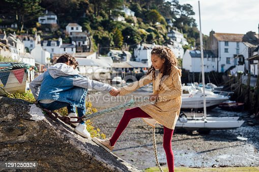 A young boy sitting on a rock wall being helped to stand up by his sister, who is holding his hand and pulling him. She is also pulling on a rope with her other hand, to aid her strength. They are on vacation in Polperro, Cornwall.