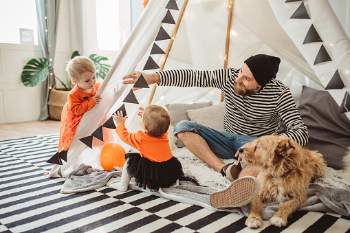 Cheerful Father With daughters celebrating Halloween At Home. They fooling around and wear costumes, they sitting in tent, home is decorated, dog is with them too