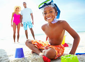 Boy sitting on the beach with parents in the background