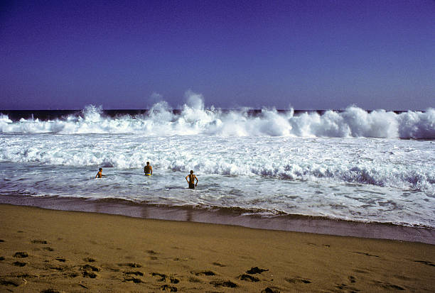 Playing in the waves, circa 1980 A few young adults playing in the waves at Newport Beach in Southern California. hearkencreative stock pictures, royalty-free photos & images