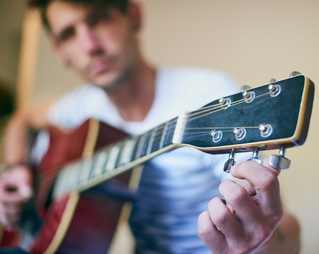 Shot of a handsome young man playing guitar at home