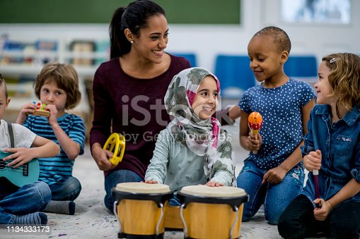 A multi-ethnic group of young school children are indoors in their classroom. Their teacher is watching them playing instruments together. The instruments include drums, maracas, and a guitar.