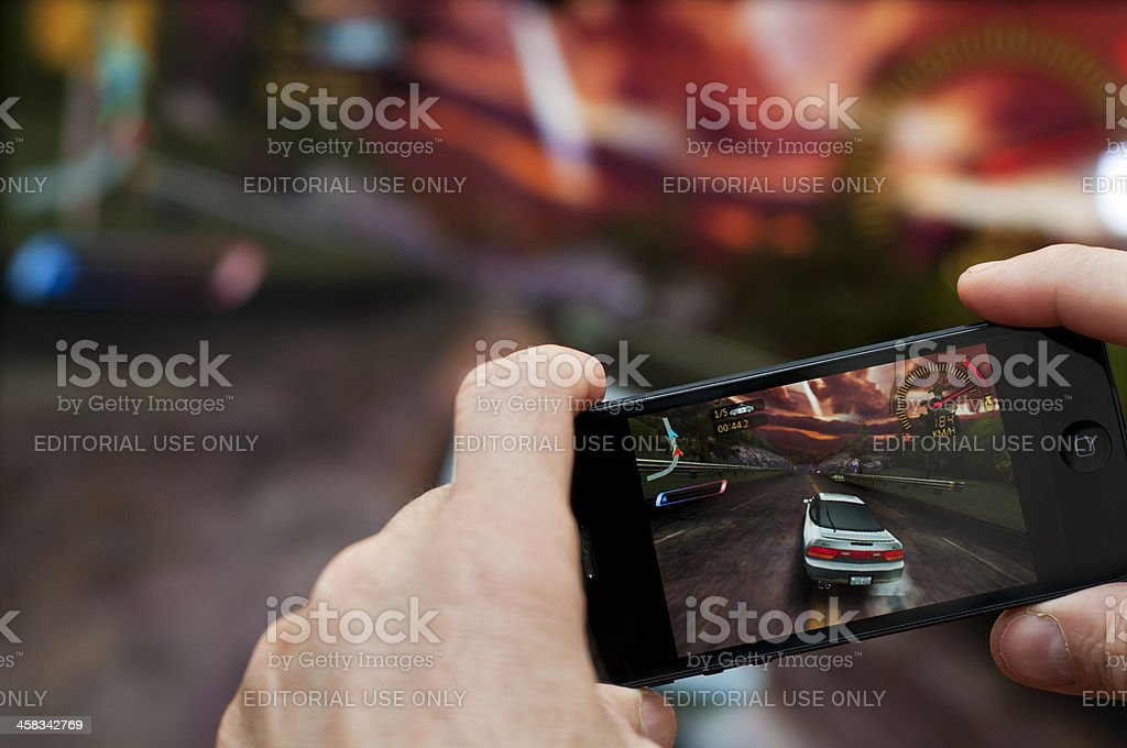 Playing iPhone 5 game on big screen via Apple TV stock photo