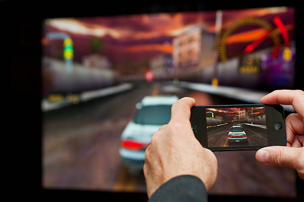 Playing iPhone 5 game on big screen with Apple TV stock photo