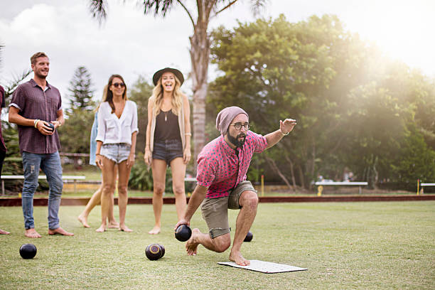 Playing Lawn Bowling Group of Australian friends playing lawn bowling late in the afternoon. leisure games stock pictures, royalty-free photos & images