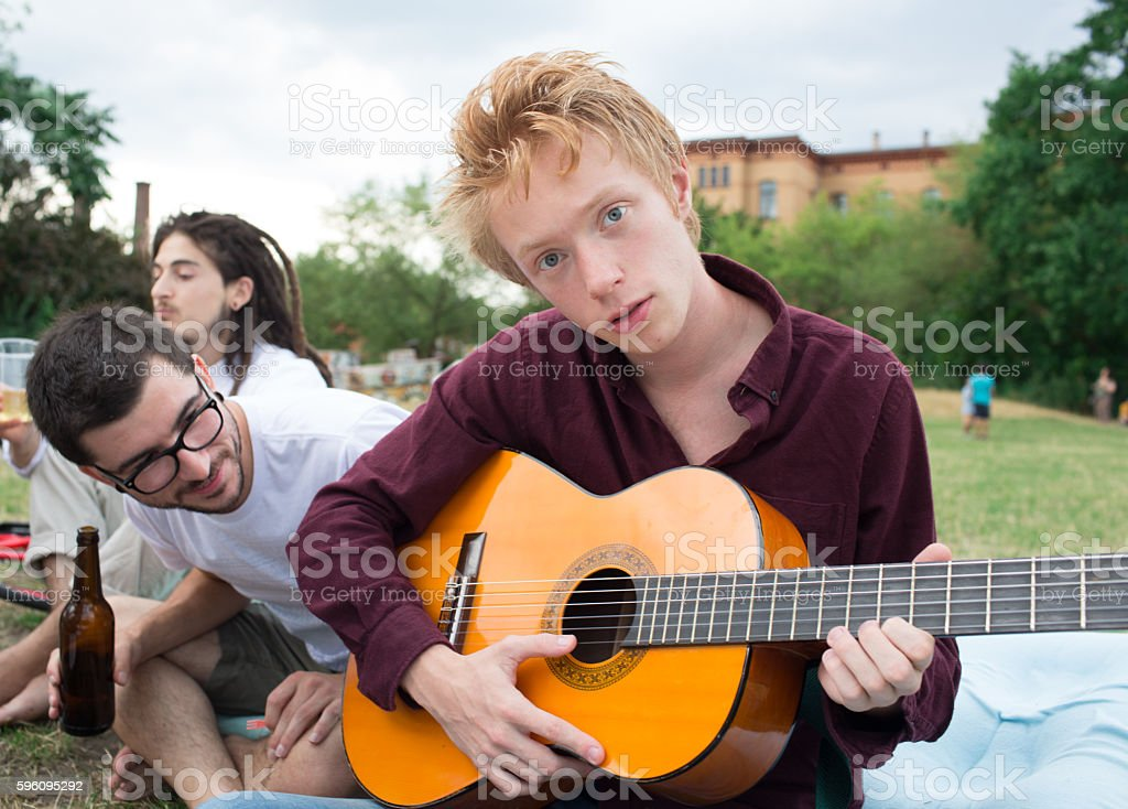 Playing music for friends in a park. Selective focus royalty-free stock photo