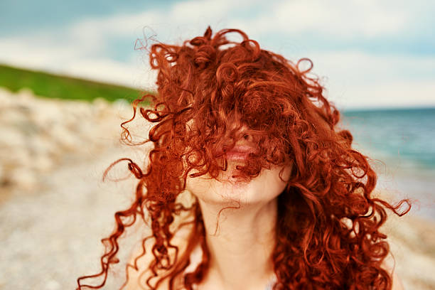 playing on beach portrait of woman with curly red hair covering her face, playing on beach, vacation concept. redhead stock pictures, royalty-free photos & images